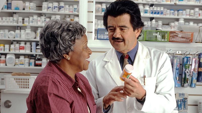 A pharmacist is talking with a patient about a drug.